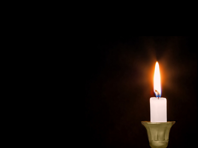 Close up of white wax lit candle on isolated black background